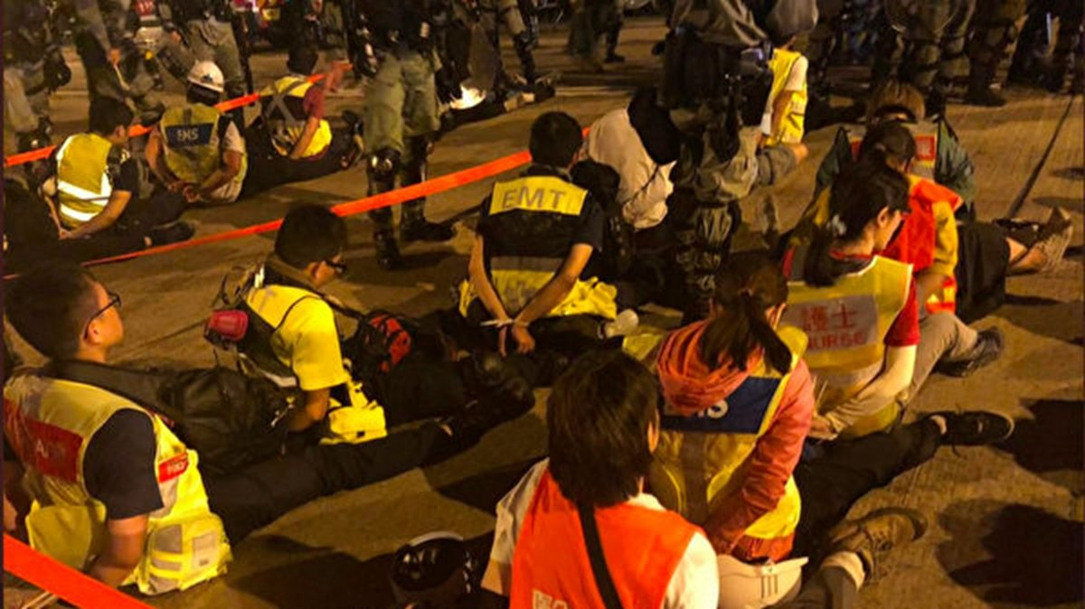 香港眾志成員羅冠聰18日在推特發佈一張照片,顯示進入理大人道救援的醫護人員被雙手反銬團坐地上,猶如押解犯人。(翻攝自羅冠聰推特)