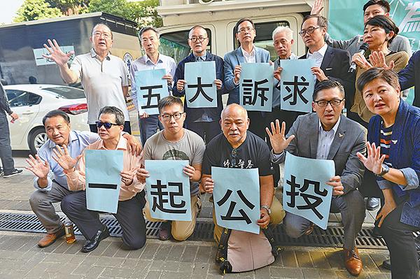 昨日下午,128位民主派區議會候選人、現任立法會議員齊聚政府總部前的公民廣場外,共同呼籲市民用選票「制止警暴」。(宋碧龍/大紀元)