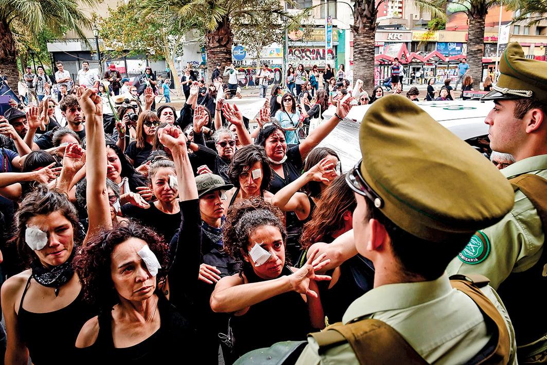 眼睛受傷的示威者已成智利抗議象徵。11月1日,民眾蒙上一隻眼睛進行抗議。(Getty Images)