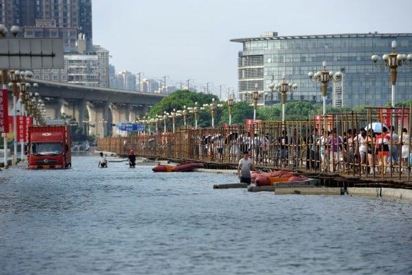 武漢湯遜湖大橋被淹,武漢投入近40萬元人民幣,在湯遜湖大橋橋面架起一條1200米長、寬2米的人行棧道,猶如一條橋上橋。圖為2016年7月10日下午,武漢湯遜湖大橋臨時占道已完成所有鋪設工程,幾位工人師傅正在進行最後的加固工序,並轉運剩餘耗材。(大紀元資料室)