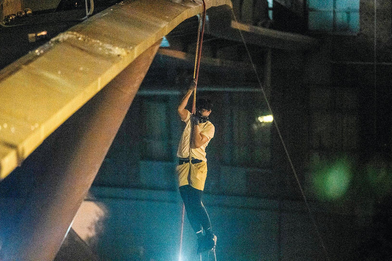 香港理工大的部份抗爭者,靠繩索從人行天橋垂降到公路逃離。(ANTHONY WALLACE/AFP via Getty Images)