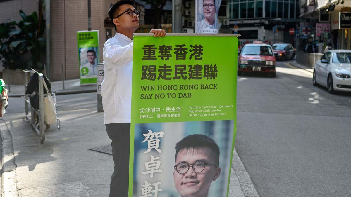 一名香港民主派人士參選區議員,其競選口號包括「踢走民建聯」、「五大訴求,缺一不可」等。(PHILIP FONG/AFP via Getty Images)
