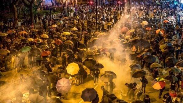 圖為上萬名港人湧上街頭,趕往遭警察重重包圍的理工大學營救學生,遭到警方催淚彈,水炮車強力阻截。(DALE DE LA REY/AFP via Getty Images)