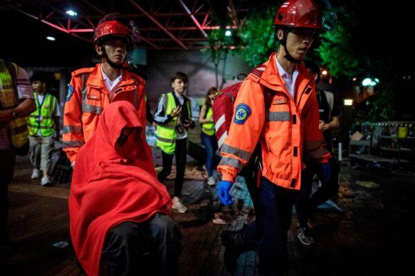 香港理工大學校園內2019年11月24日有醫護人員帶著坐在輪椅上身體虛弱的抗爭者(前左)走向一輛救護車。至今仍有數十名抗爭者被警方圍困在校園內。(NICOLAS ASFOURI/AFP via Getty Images)