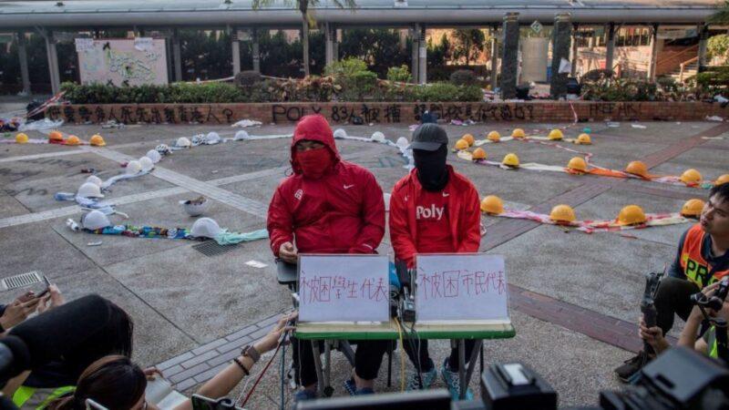 香港理工大學校園內兩名留守者2019年11月24日代表仍被圍困在校園內的其他數十名抗爭者向進入校園採訪的媒體發表講話。(NICOLAS ASFOURI/AFP via Getty Images)