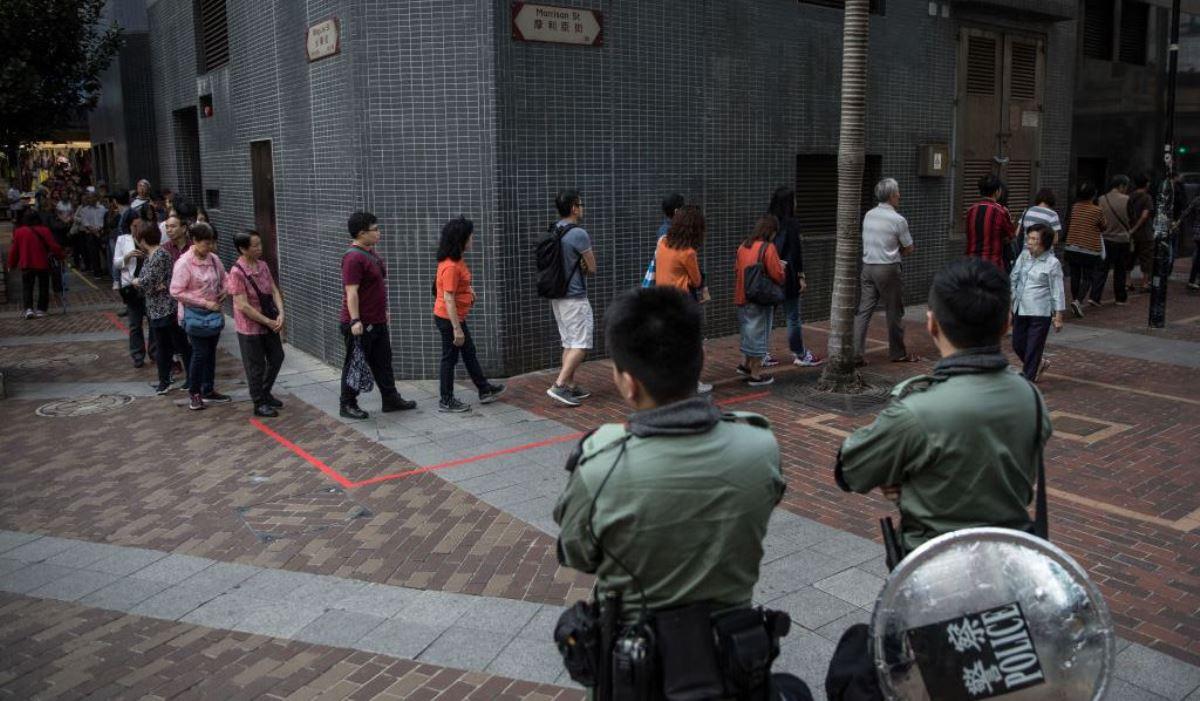 香港民眾2019年11月24日在警察的警戒下在投票站排隊為區議會選舉投票。(CHRIS MCGRATH/GETTY IMAGES)