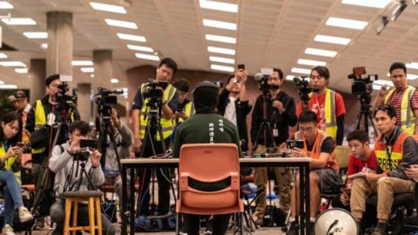 香港理工大學留守抗爭者27日深夜召開記者會發出聲明,對警方要進入校園的行動感到憤怒,指警方撤封校園後,留守者自會離開。(Anthony Kwan/Getty Images)