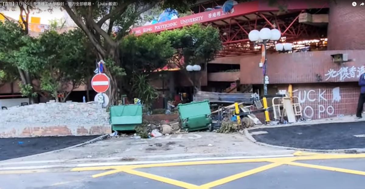 今日(11月29日)香港理工大學在經過了整整12天的圍困後終於解封,警方全部撤離,而理大校方支援則安排了一些保安人員進入校園內進行搜索和清理,理大管理層還安排了外籍保安人員守住學校的各個路口以及被挖開的校園外的鐵絲網。(影片截圖)