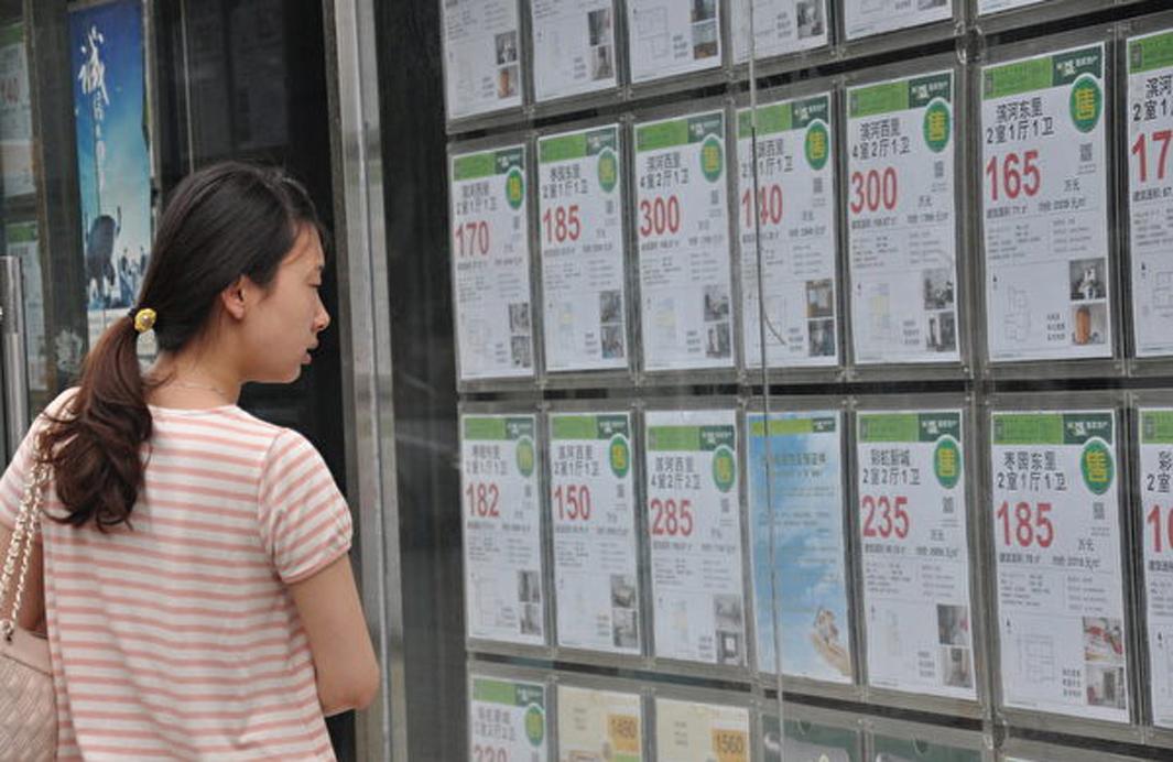 為北京一市民正在查看房產中介公司貼出的資訊。 (大紀元資料室)