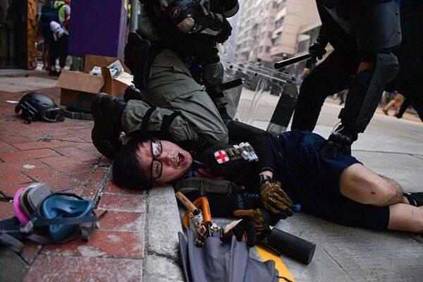 圖為港警在灣仔地區暴力拘留一名抗爭者。(NICOLAS ASFOURI/AFP/Getty Images)