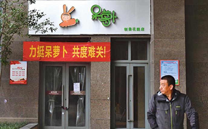 近日,合肥眾多關門的呆蘿蔔門店上懸掛起「力挺呆蘿蔔共渡難關」的橫幅。(大紀元資料室)