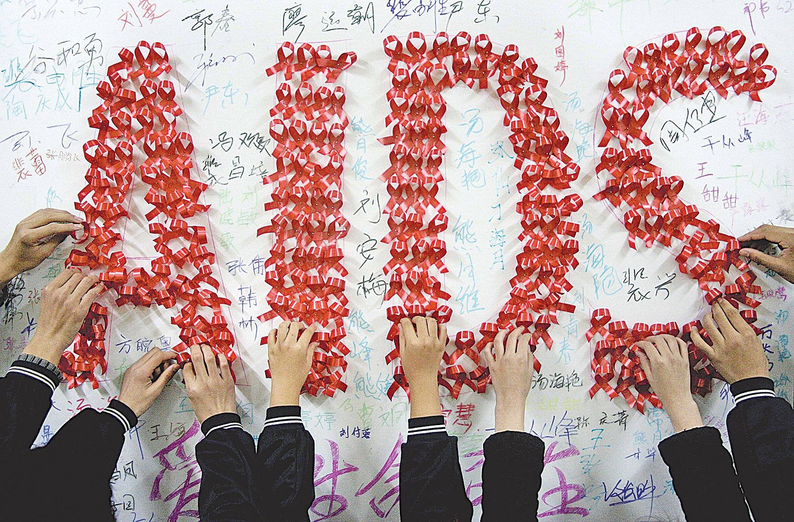 圖為2009年世界愛滋病日的前一天,中國安徽省漢山的一所學校中,學生用手工製作的紅絲帶愛滋病標誌。當年約74萬中國人感染了愛滋病毒,10年後,中國大陸愛滋病感染病例繼續大幅增加。 (STR/AFP/Getty Images)