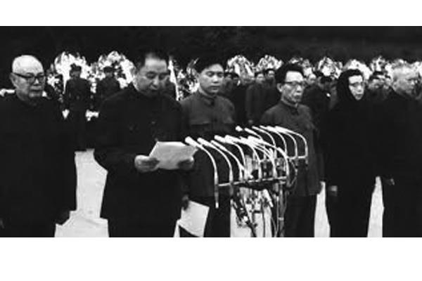 在毛澤東追悼會上,華國鋒念悼詞時,王洪文(從左到右第3個)不安地探過頭,竟然透過華的肩膀,看了看華手中拿著的悼詞稿子。(網絡圖片)