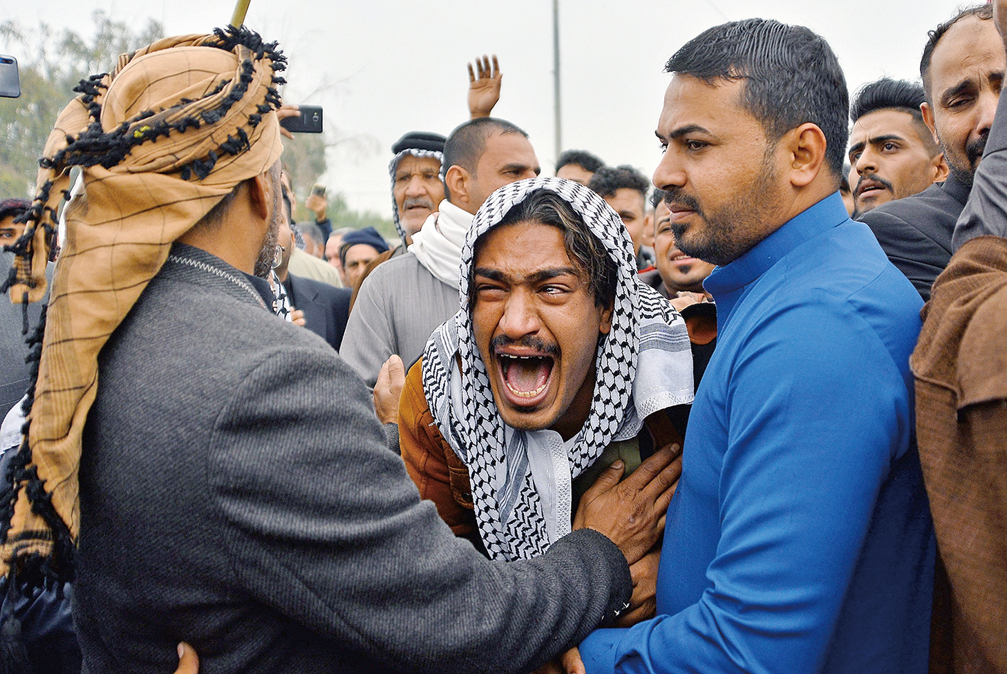伊朗當局對示威民眾採取暴力鎮壓,很多示威者被打死。圖中男子因為失去了一位兄弟而悲痛欲絕。(Getty Images)