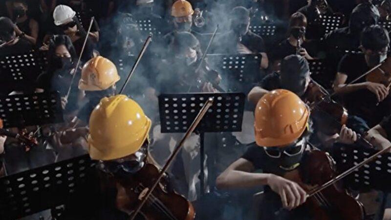 一群香港文化藝術工作者,戴著頭盔、眼罩以及防毒面罩,製作了一首管絃樂版的《願榮光歸香港》。(影片截圖)