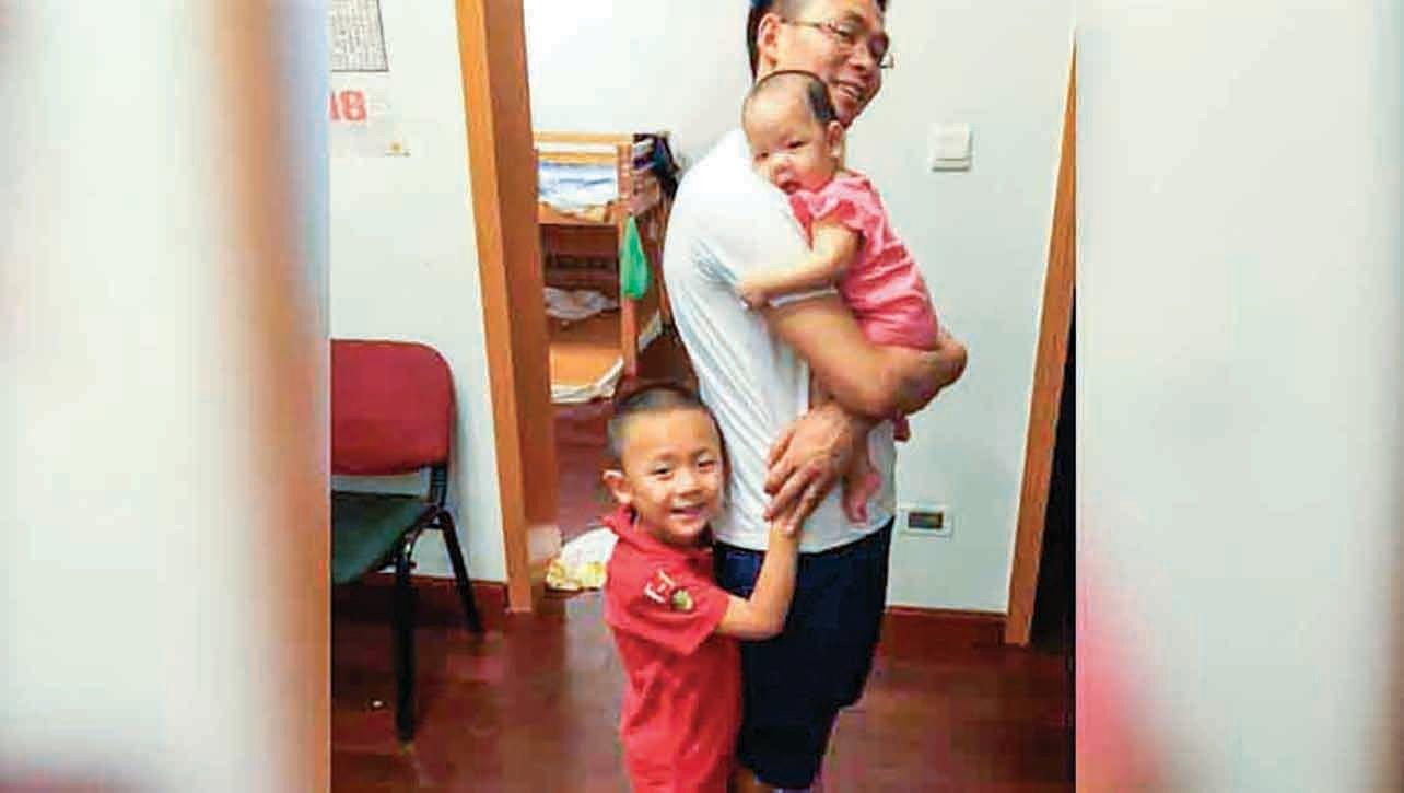成都「秋雨教會」長老覃德富與兩個孩子合照。(RFA)