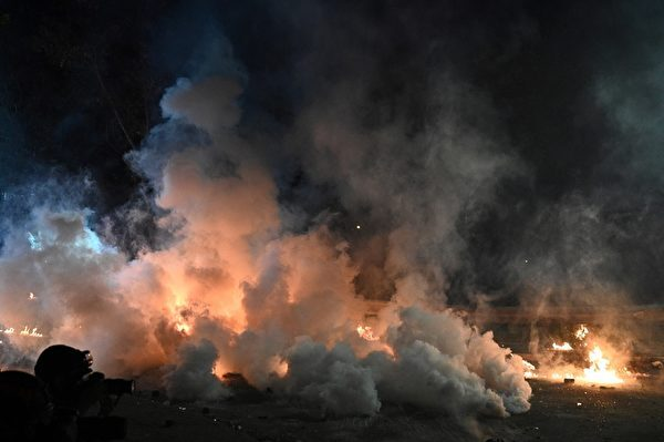 2019年11月12日,警方施放催淚彈煙霧瀰漫,地上有火苗。(Philip FONG/AFP)