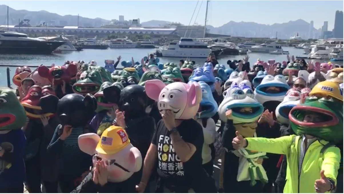 12.8國際人權日上午,城寨的粉絲團隊,帶著各式佩佩娃和連登豬大頭公仔,出現在觀塘海濱,帶給港人一個驚喜,並向世界講述著香港6個月來,反修例運動中的故事。 (影片截圖)