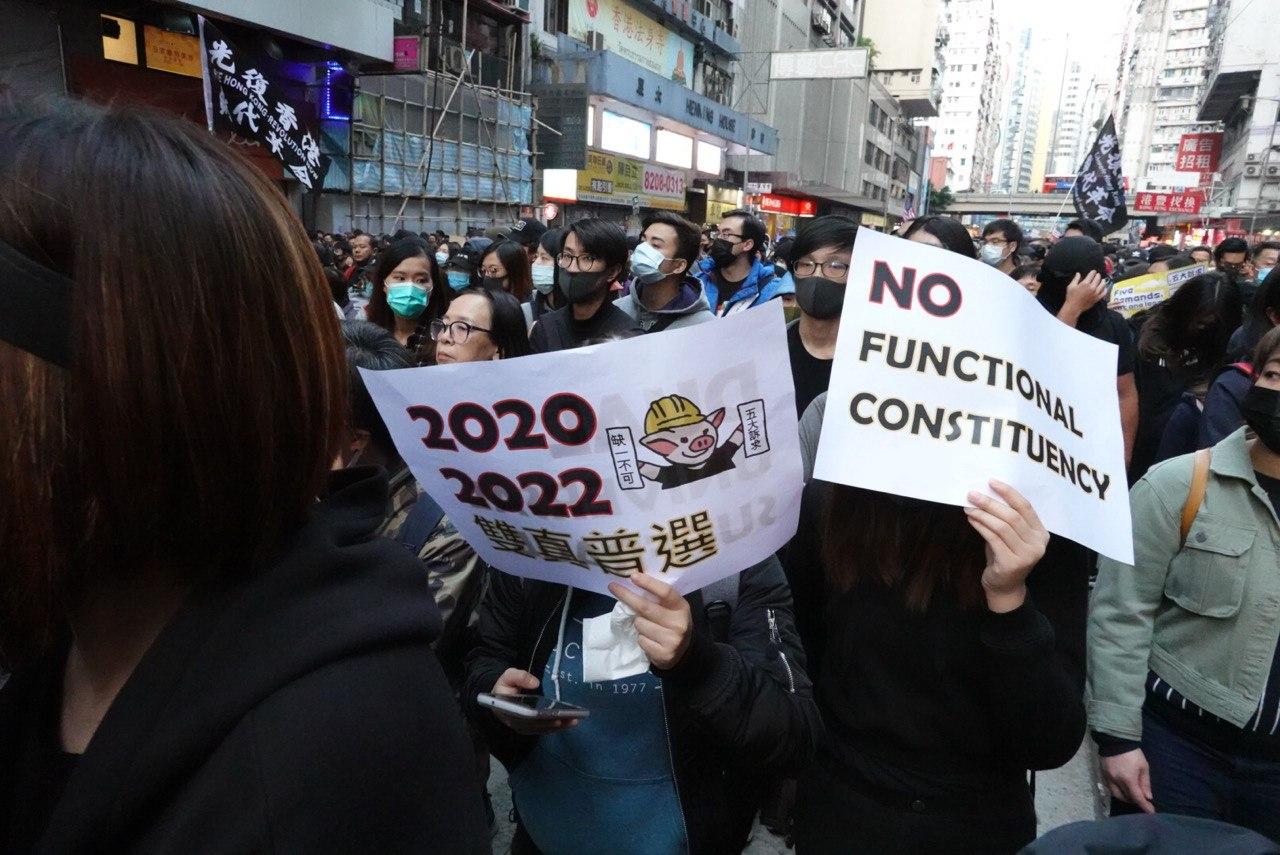 有市民舉海報表達訴求:2020、2022舉行雙真普選,以及取消功能組別。(余鋼/大紀元)