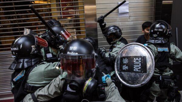香港民眾11日發起「三罷」行動,港警以真槍實彈射傷示威者,同時在全港濫射噴霧劑,槍指市民大肆抓人揮棍毆示威者。( DALE DE LA REY/AFP via Getty Images)