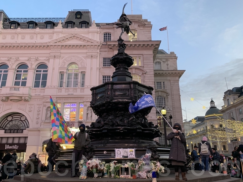 是次活動地點乃一個月前(11月8日)倫敦悼念周梓樂燭光活動的祭壇位置。除了聲援香港的遊行活動外,集會亦是為了紀念一個月前不幸離世的周梓樂同學。(唐詩韻/大紀元)