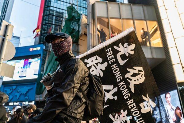 一名抗爭著舉行光復香港、時代革命的旗子。(Anthony Kwan/Getty Images)