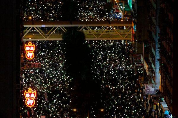 入夜後,抗議民眾紛紛打開手機自帶燈,現場一片光海,令人震撼。(ALASTAIR PIKE/AFP via Getty Images)