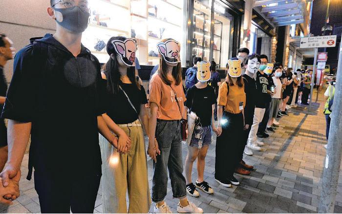 上訴庭昨日拒絕政府暫緩令申請,《禁蒙面法》正式失效。圖為10月18日市民戴上口罩和各種面具在多區築成人鏈,抗議政府實施《禁蒙面法》。( 資料圖片)