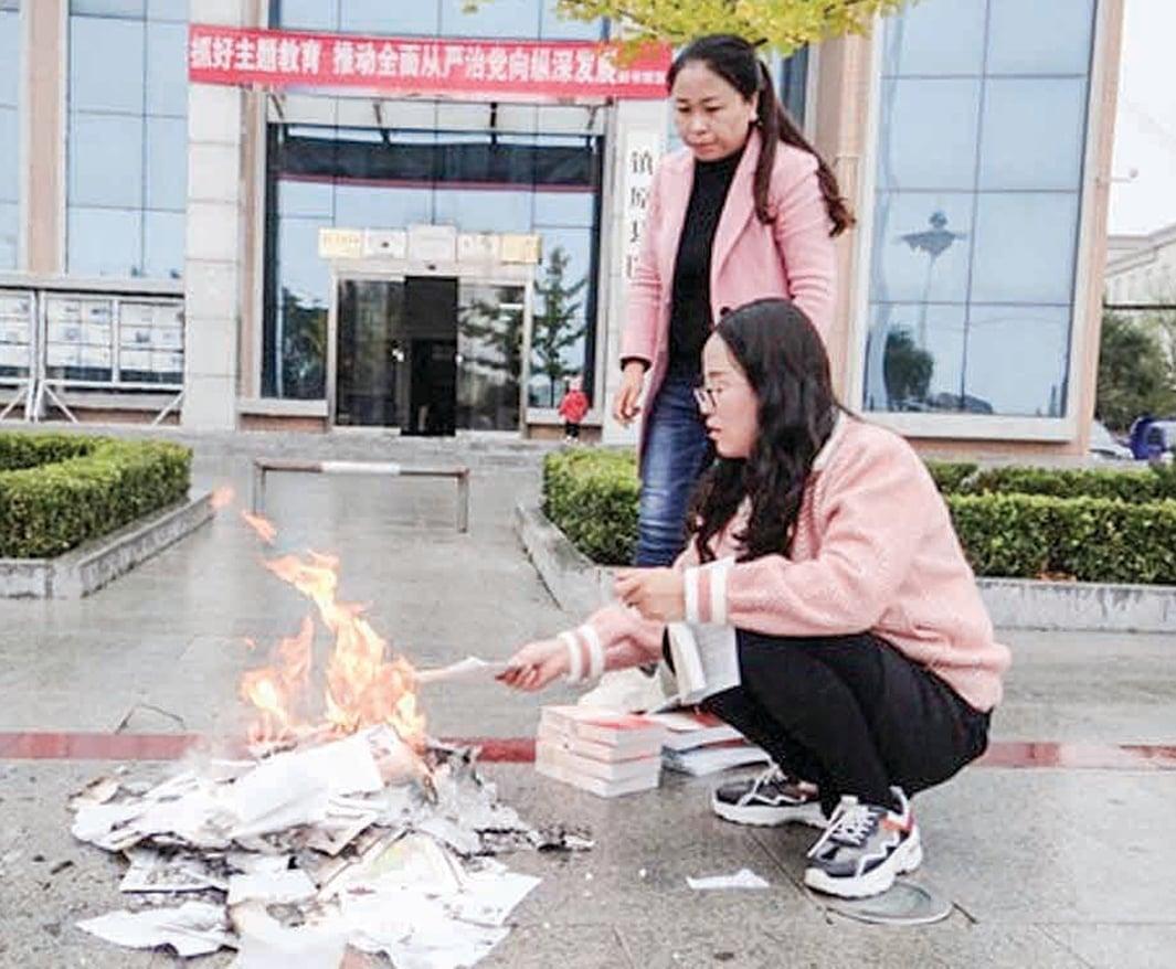 甘肅省鎮原縣圖書館工作人員正撕碎並燒燬下架的書籍。(鎮原縣圖書館官網)