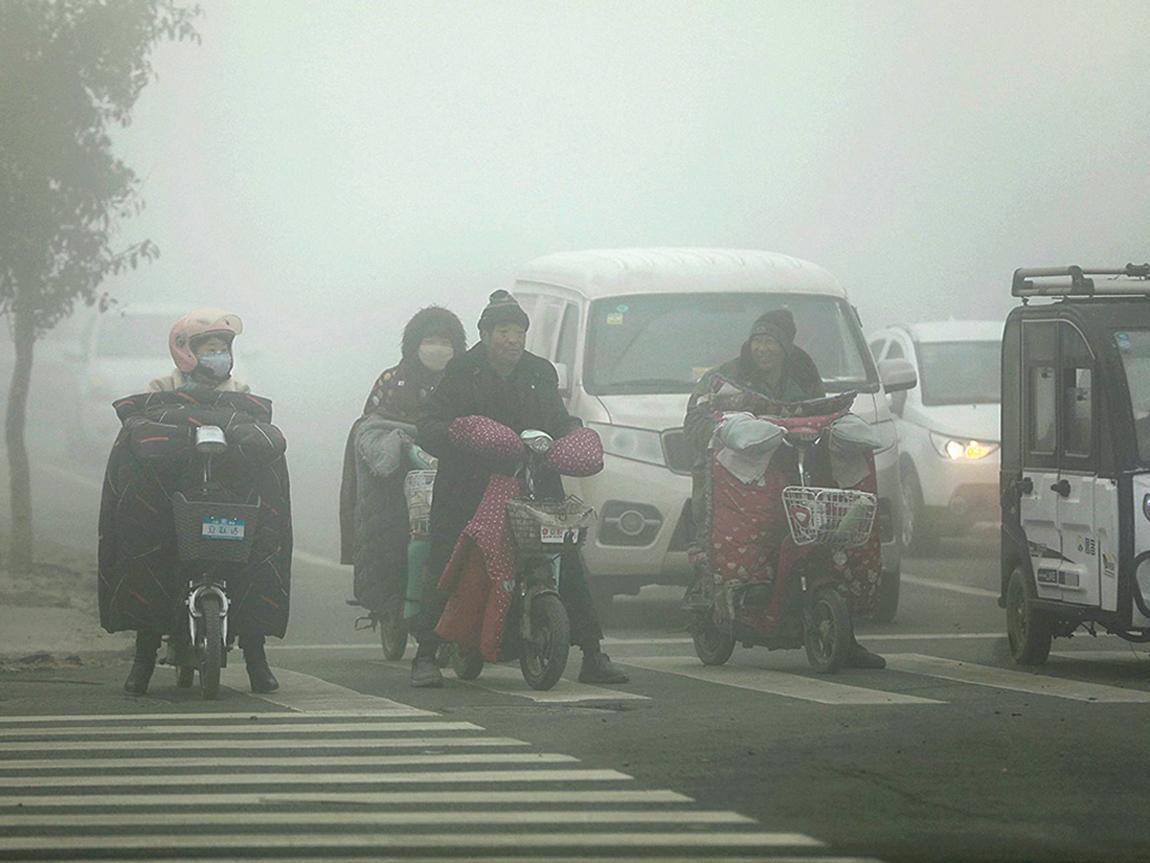 陰霾多日籠罩大陸華北、黃淮、江漢等地區。圖為近日,陰霾籠罩的山東菏澤曹縣人們在街頭騎行。(大紀元資料室)