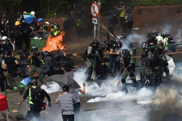 圖為,香港理工大學校園內,抗議者(左)試圖逃離防暴警察(右)的逮捕。(YE AUNG THU/AFP via Getty Images)