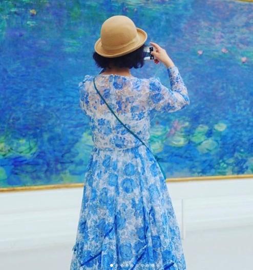 拿著相機忙著拍攝的女遊客,不知道後面也有相機正在拍她呢!衣服的色調和眼前的畫作非常調和,像夏天微風吹過開滿花草的湖面。