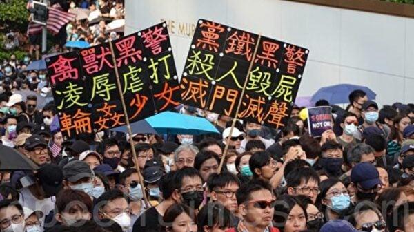 9月8日,香港市民手舉寫著「獸禽黑警 凌辱虐打 輪姦少女」等各式標語遊行。(余鋼/大紀元)