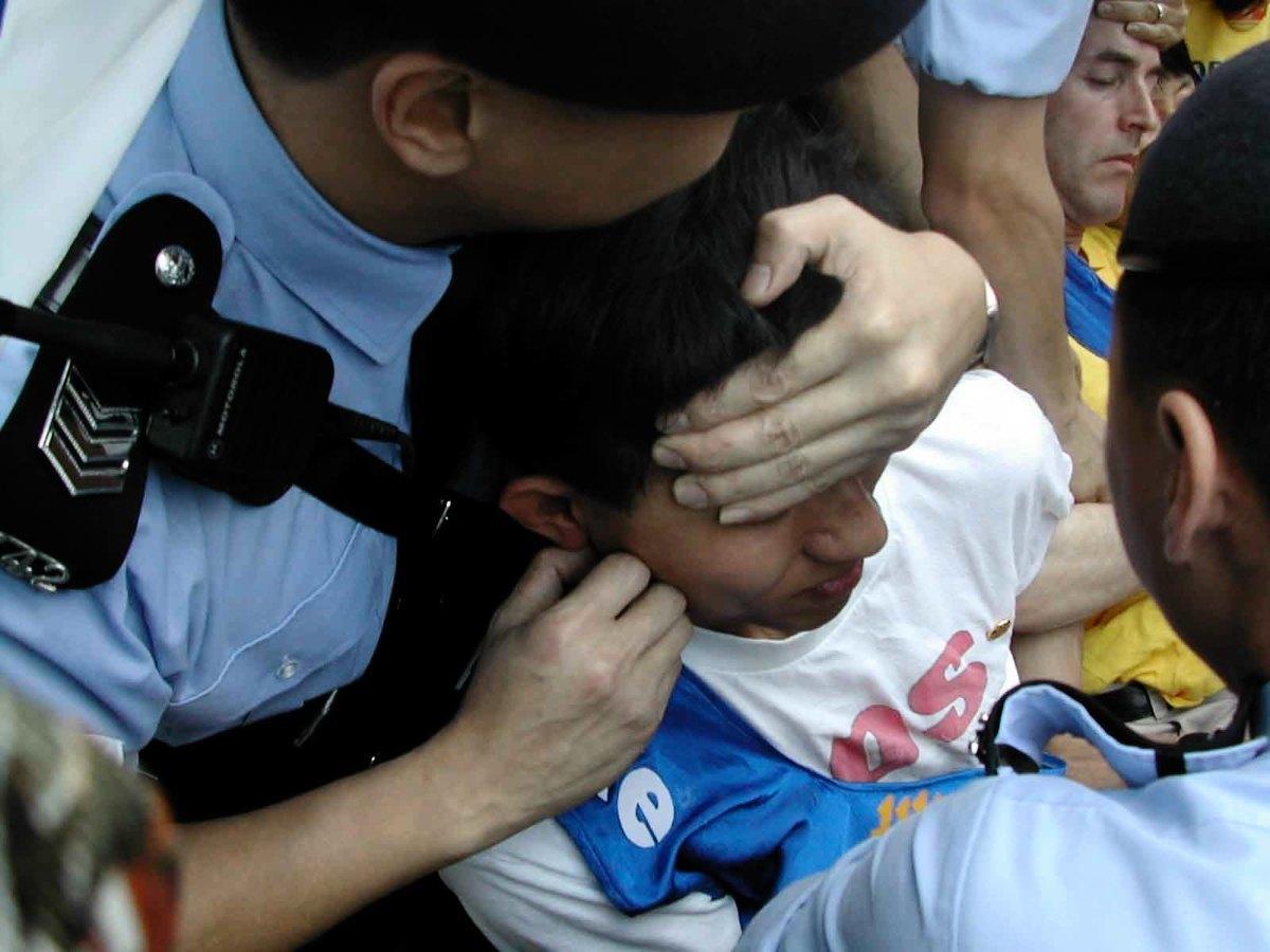 16名當日在中聯辦外請願的法輪功學員,每人被四五名警員粗暴地抓臉、扯頭、按太陽穴等穴位,然後架起請願者的雙手、雙腳將他們抬上警車,送往警署。(大紀元資料圖片)
