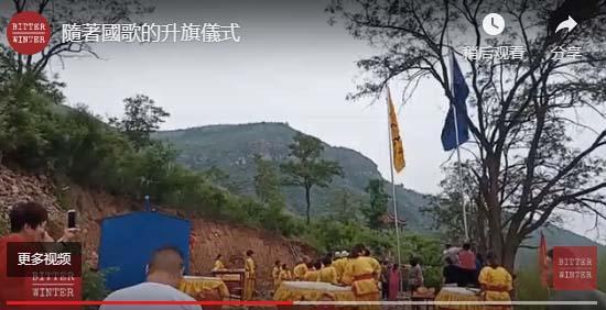 圖為「廟宇」外,伴隨著中共「國歌」,升起一面藍旗和寫有「通天大令」字樣的黃旗。(影片截圖)