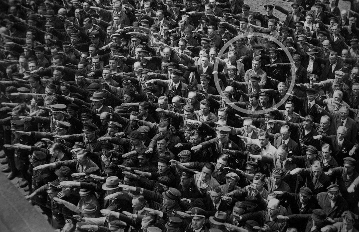 在1991年被公開的照片,拍攝於1936年6月13日,地點是德國漢堡的布隆福斯造(Blohm+Voss)船廠,當時工人們舉行盛大的集會,慶祝一艘德國海軍訓練船啟航。所有人都在向元首行納粹禮,只有一位名字叫August Landmesser的造船工人雙手抱胸拒絕行禮。(公有領域)