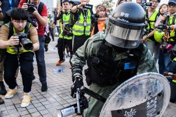 12月22日,一名港警掏出手槍威嚇抗議市民。(ANTHONY WALLACE/AFP via Getty Images)