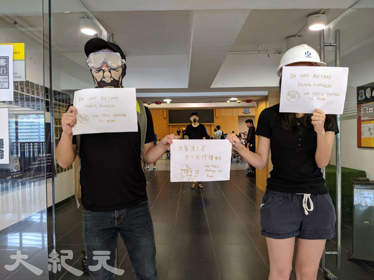 2019年9月23日,香港中大善衡書院,學生在美心經營的食堂出口手拿標語。(黃曉翔/大紀元)