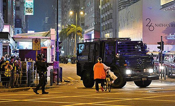 圖為一名推單車的婆婆在尖沙咀街頭,勇對裝甲車,大罵警察。(文瀚林/大紀元)