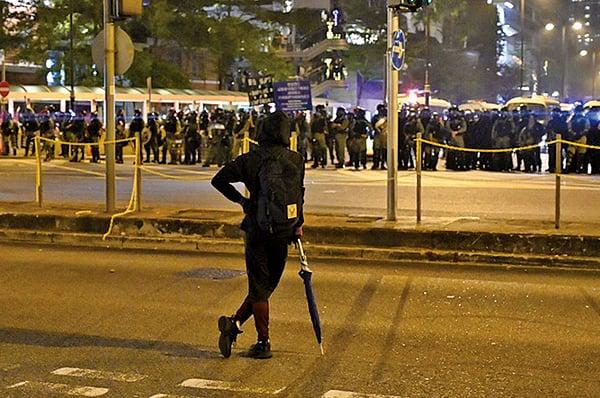 圖為平安夜,一名抗爭者在尖沙咀從容面對成群結隊防暴警察。(文瀚林/大紀元)