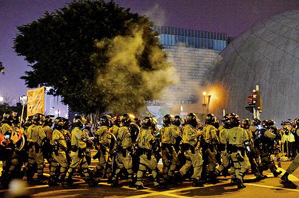 圖為平安夜,防暴警察在尖沙咀梳士巴利道施放催淚彈,並舉橙旗警告會開槍。(宋碧龍/大紀元)