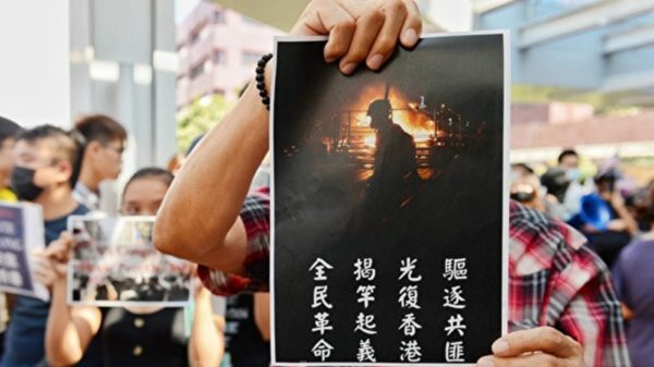 圖為9月20日,港人展示海報,驅逐共黨、光復香港、揭竿起義、全民革命。(宋碧龍/大紀元)