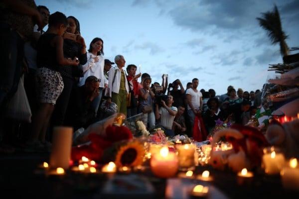 伊斯蘭國於2016年7月15日宣稱,在法國尼斯海灘大道屠殺84人的卡車司機是該組織的士兵。法警方隨後迅速逮捕凶手的妻子及兩個夥伴進行偵訊。本圖為15日,民眾聚集在屠殺現場為罹難者哀悼。(Carl Court/Getty Images)