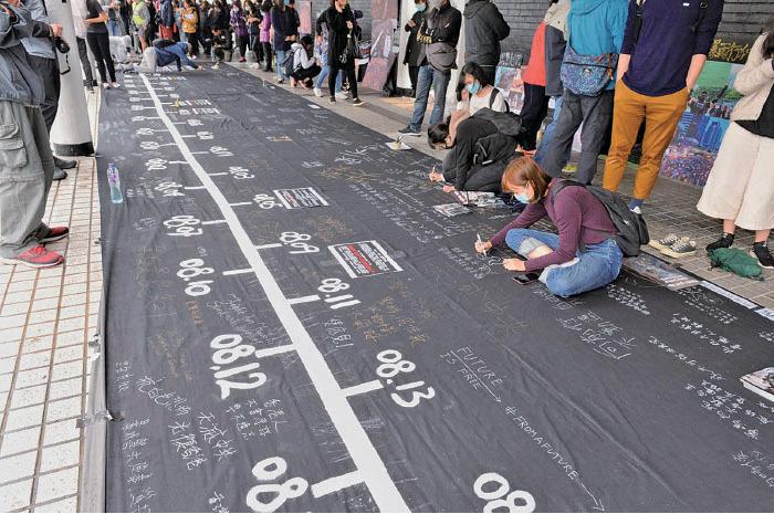 大會在愛丁堡廣場設置一塊3米乘38米的黑色「連儂布」,寫有半年來發生警民衝突、黑社會恐襲市民的重要日子,供市民寫下心聲。(宋碧龍/大紀元)