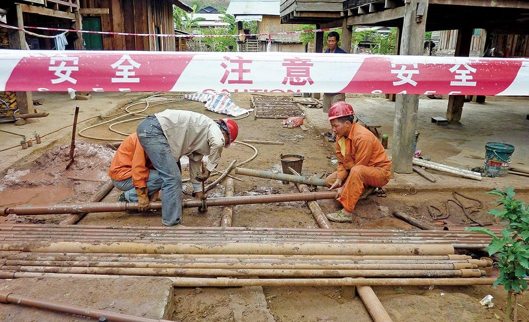 圖為2011年3月11日,中國工人在老撾北部為鐵路的興建做準備工作。(Getty Images)