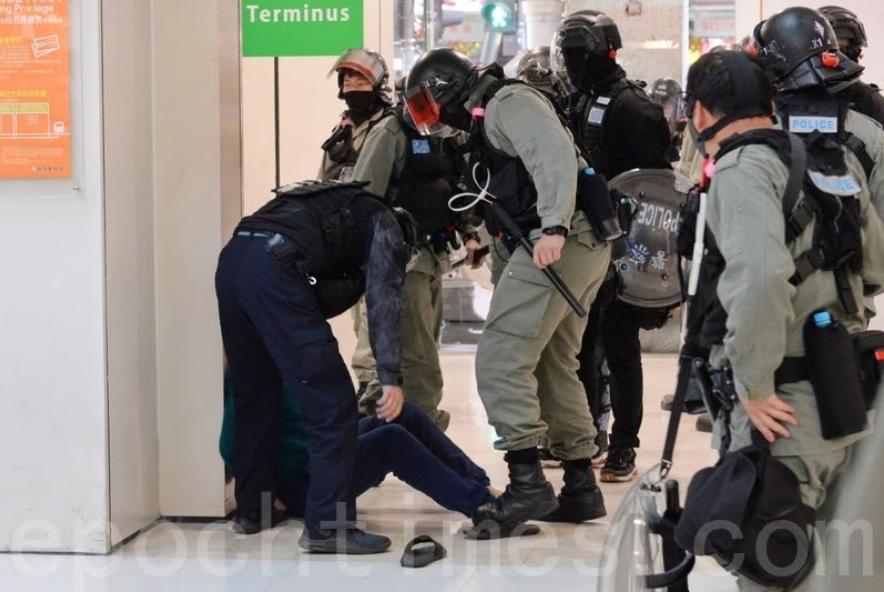 2019年12月26日,香港網民發起「和你SHOP蒙面日」,到大埔超級城等大型商場聚集,防暴警察逮捕抗爭者,抗爭者已被雙手被拷靠牆,黑警還暗地裡小動作打人。(宋碧龍/大紀元)