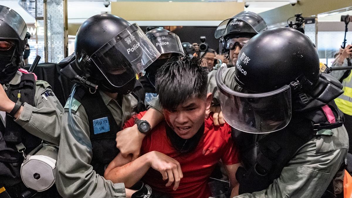 推特上流傳的影片顯示,黑警疑似用鋒利的盾牌割抗爭者脖子。(Anthony Kwan/Getty Images)
