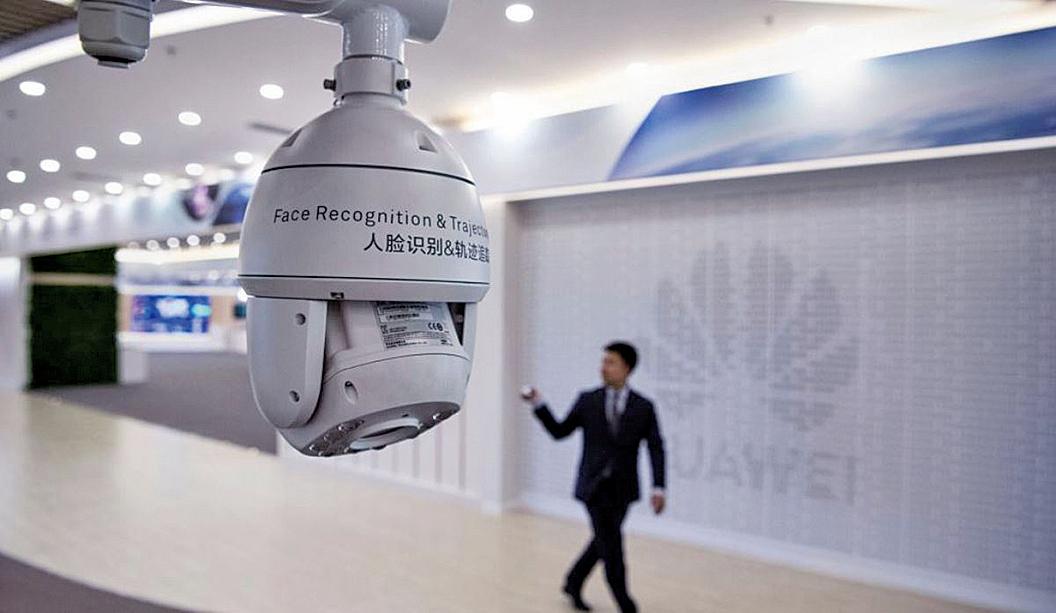 圖為2019年4月26日中國深圳華為公司阪田基地一名華為工作人員從人臉識別監控攝像頭前走過。(Getty Images)