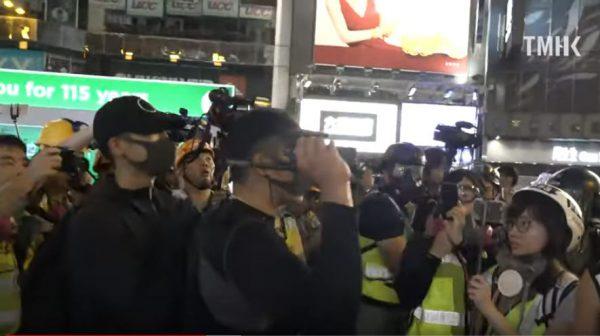 8月11日抗議人群中出現了手持伸縮式警棍的黑衣人配合警方抓捕抗議者。(影片截圖)