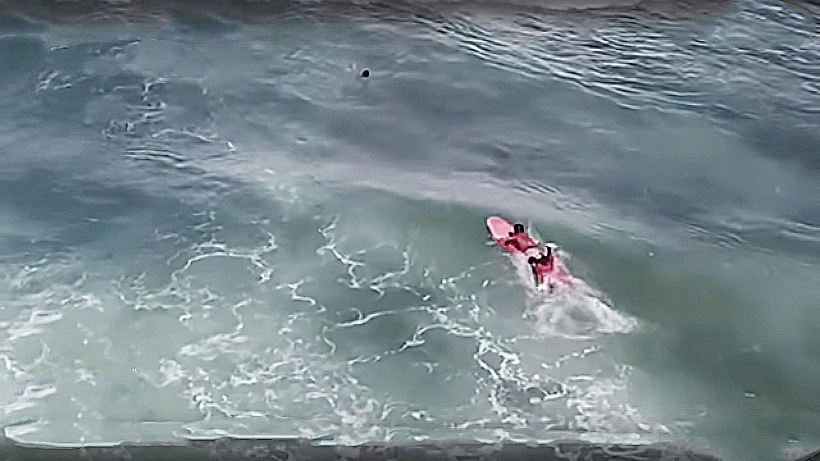 航拍機拍到菲律賓選手羅傑放棄比賽去救被大浪打中,差點被大海吞噬的印尼選手阿里普(紅圈處)。(影片截圖)
